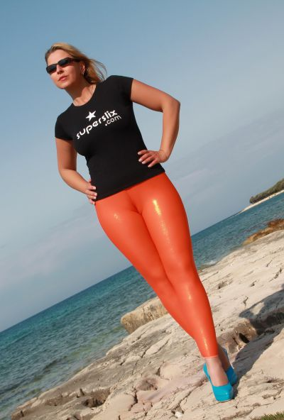 Photo №1 Big ass mature blonde Desyra Noir posing in orange latex pants on the beach