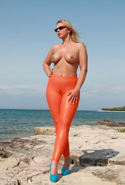 Photo №12 Big ass mature blonde Desyra Noir posing in orange latex pants on the beach