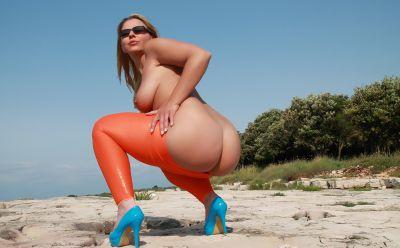 Photo №15 Big ass mature blonde Desyra Noir posing in orange latex pants on the beach