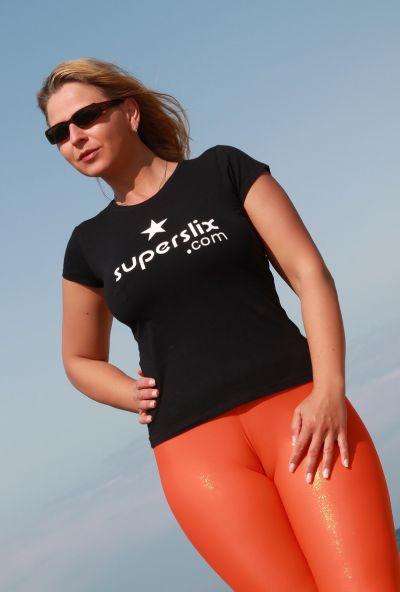 Photo №2 Big ass mature blonde Desyra Noir posing in orange latex pants on the beach