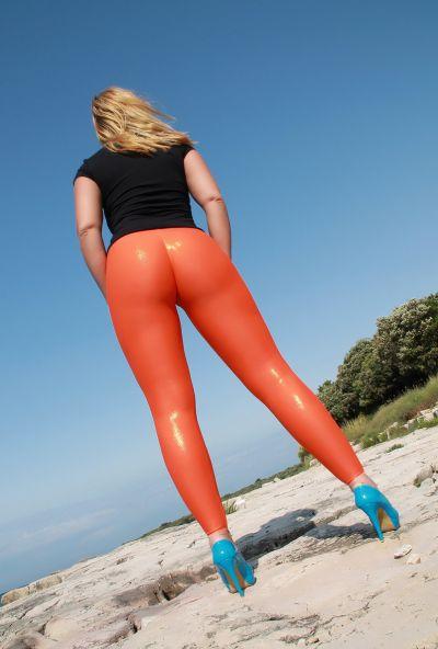 Photo №4 Big ass mature blonde Desyra Noir posing in orange latex pants on the beach