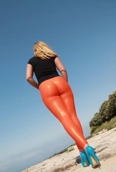 Photo №5 Big ass mature blonde Desyra Noir posing in orange latex pants on the beach
