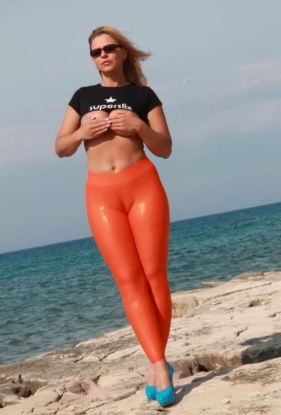 Photo №7 Big ass mature blonde Desyra Noir posing in orange latex pants on the beach