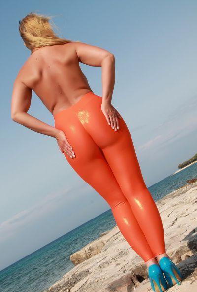 Photo №8 Big ass mature blonde Desyra Noir posing in orange latex pants on the beach