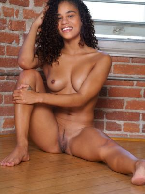 Young curly-haired mulatto Scarlit Scandal undressed and posing for the camera
