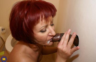 Photo №16 Redhead mature mom Monika fucks big black dick at gloryhole in the toilet